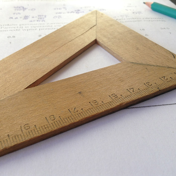 Wooden ruler placed on top of a piece of paper - representing product sizes available from CrushTag